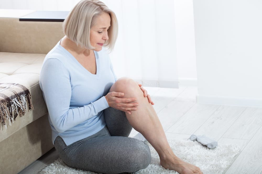 middle aged woman suffering from pain in leg at home
